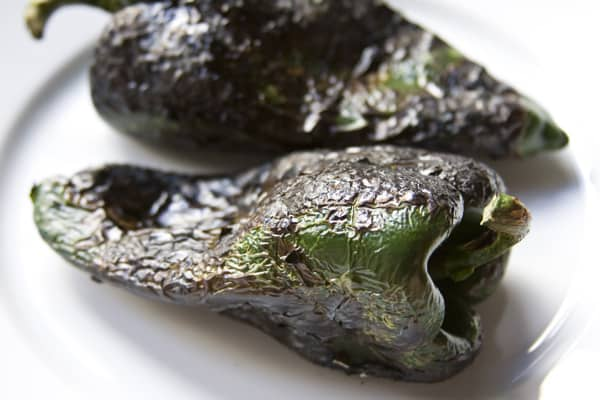 Step-by-step instructions on how to roast poblano peppers using a gas stove, comal or barbecue grill from theothersideofthetortilla.com