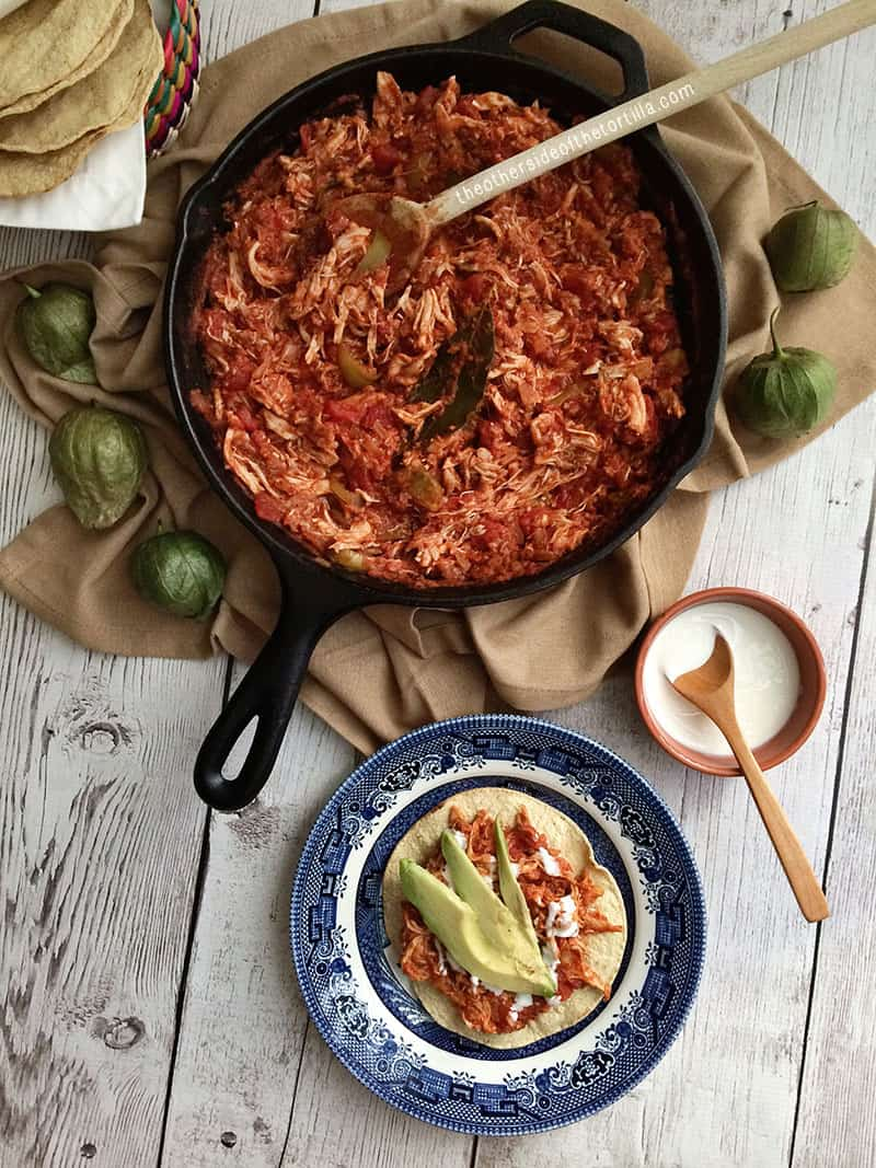 How to make tinga poblana, a Mexican dish with a tomato base and shredded chicken. Great for tostadas, tacos, served with rice, or as a quesadilla! This dish is also sometimes known as tinga de pollo or chicken tinga. Recipe via @MauraHernandez on The Other Side of The Tortilla.