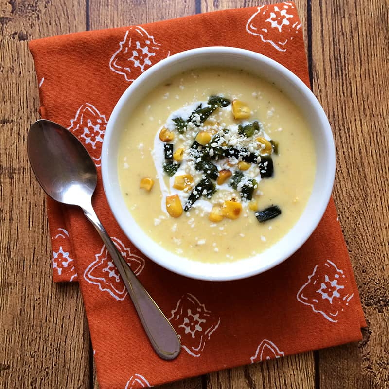 How to make Mexican crema de elote soup, garnished with roasted corn, diced poblano chile, crema mexicana and crumbled cotija cheese. Get more Mexican recipes at theothersideofthetortilla.com.