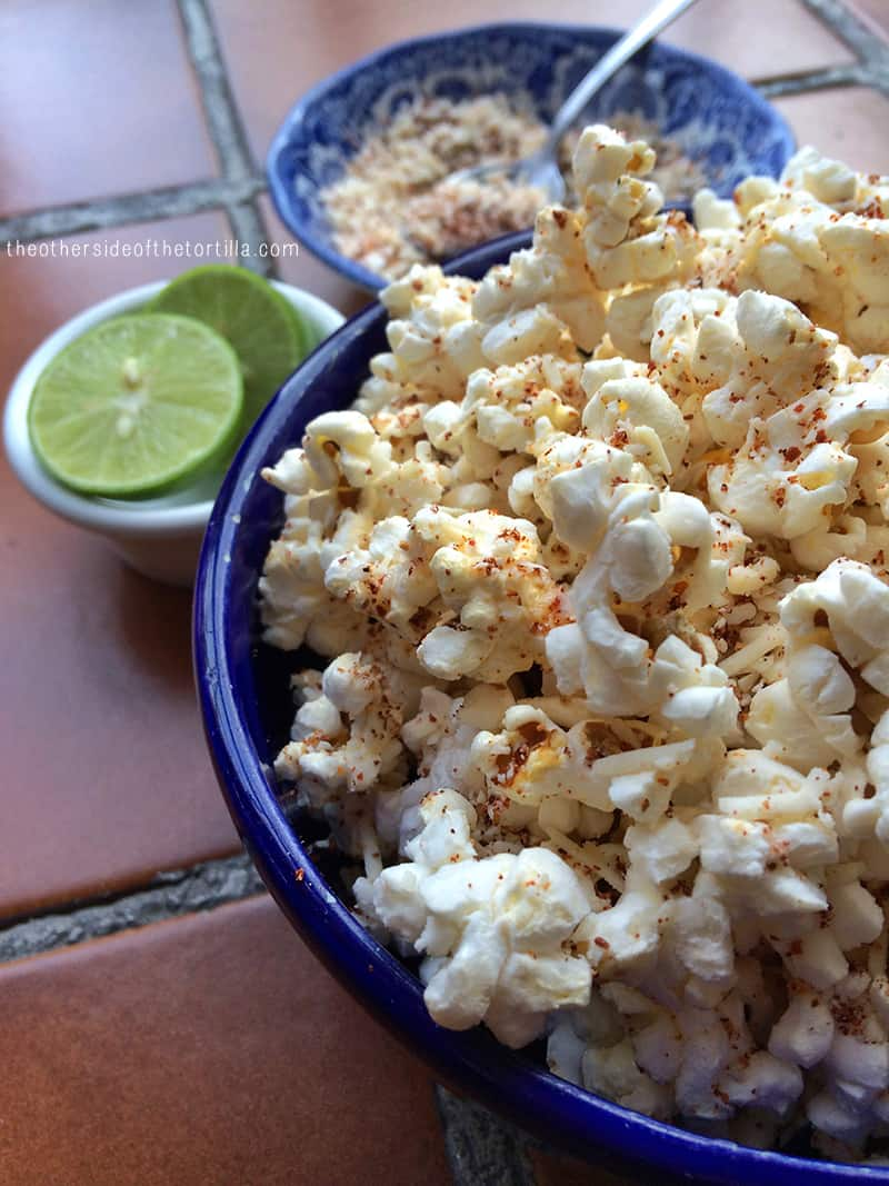How to make cheesy, spicy popcorn with queso cotija, chile powder, butter and lime juice. Recipe via theothersideofthetortilla.com.