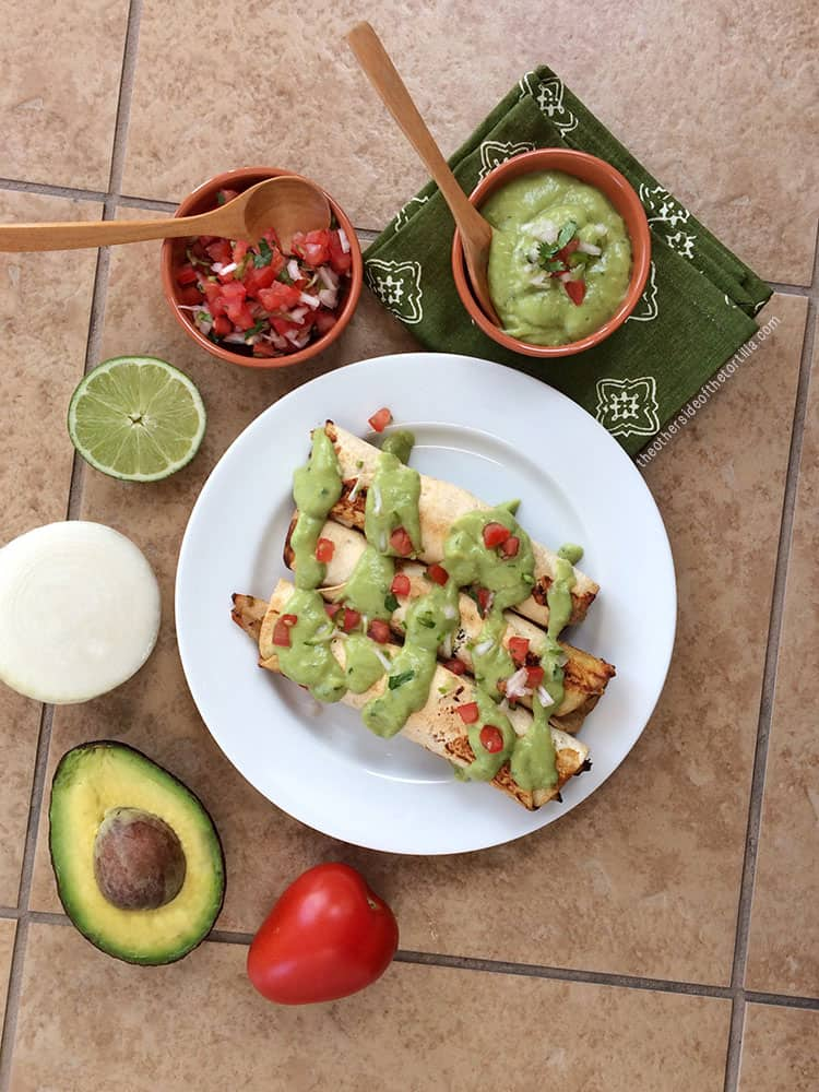 baked chicken taquitos surrounded by salsa, lime, onion, avocado and tomato on a beige tile counter top