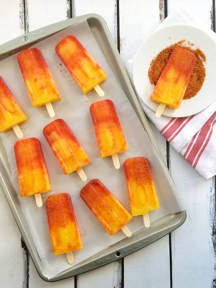 mangonada popsicles displayed on a baking sheet and a plate with tajín chili lime salt for dipping