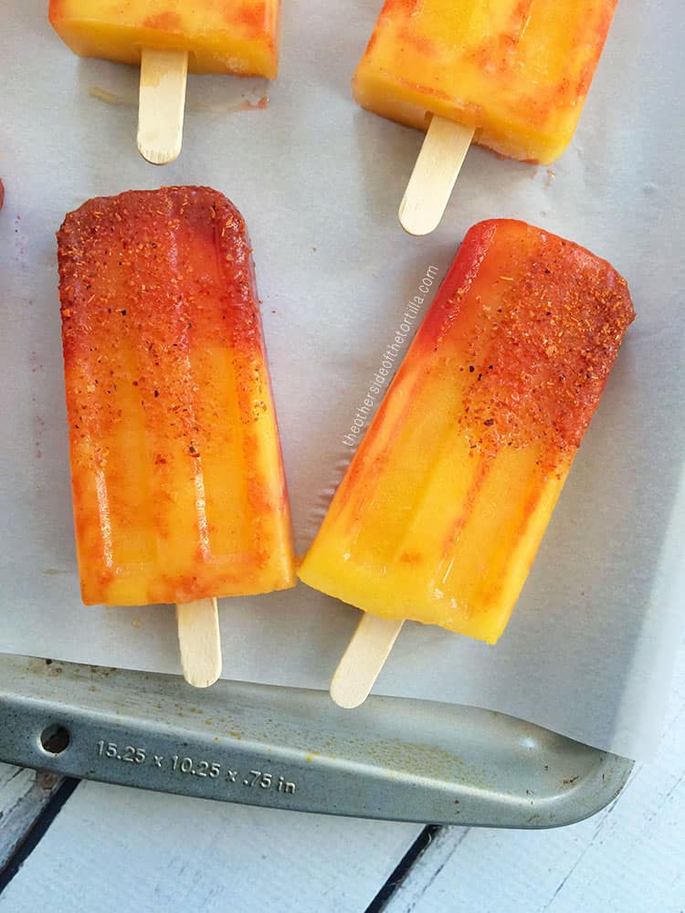 Close-up of mangonada popsicles that are red, orange and yellow