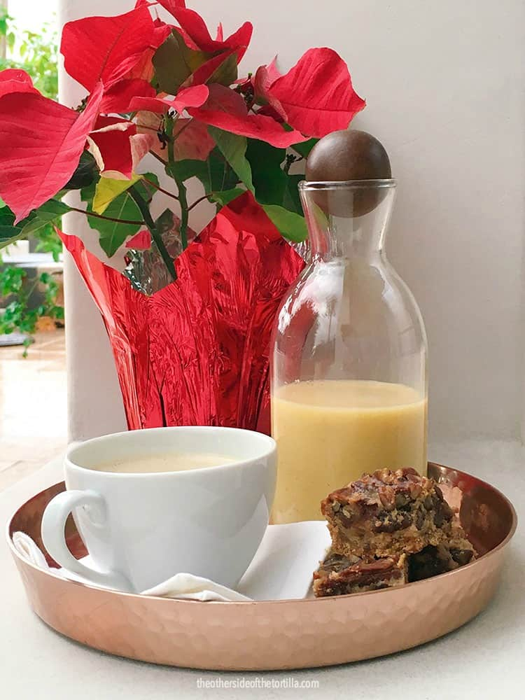 Rompope, also known as Mexican eggnog, served with holiday treats next to poinsettia flowers