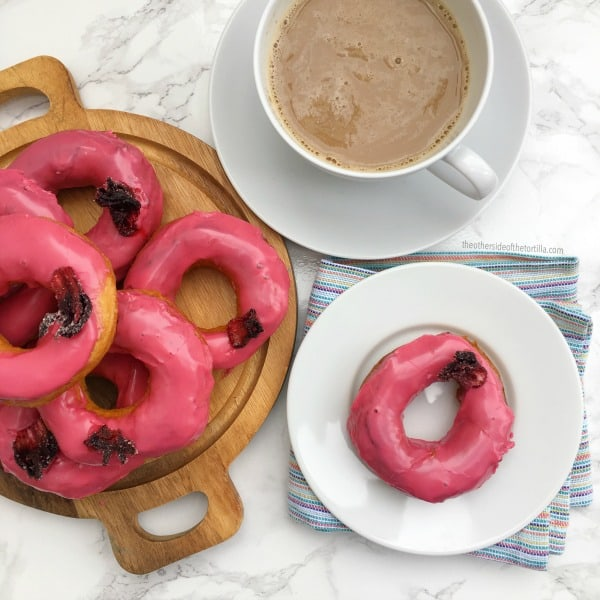 Impress everyone with this super-easy recipe for hibiscus-glazed doughnuts. They look fancy but you won't believe how easy and quick they are to make! See more Mexican recipes at theothersideofthetortilla.com