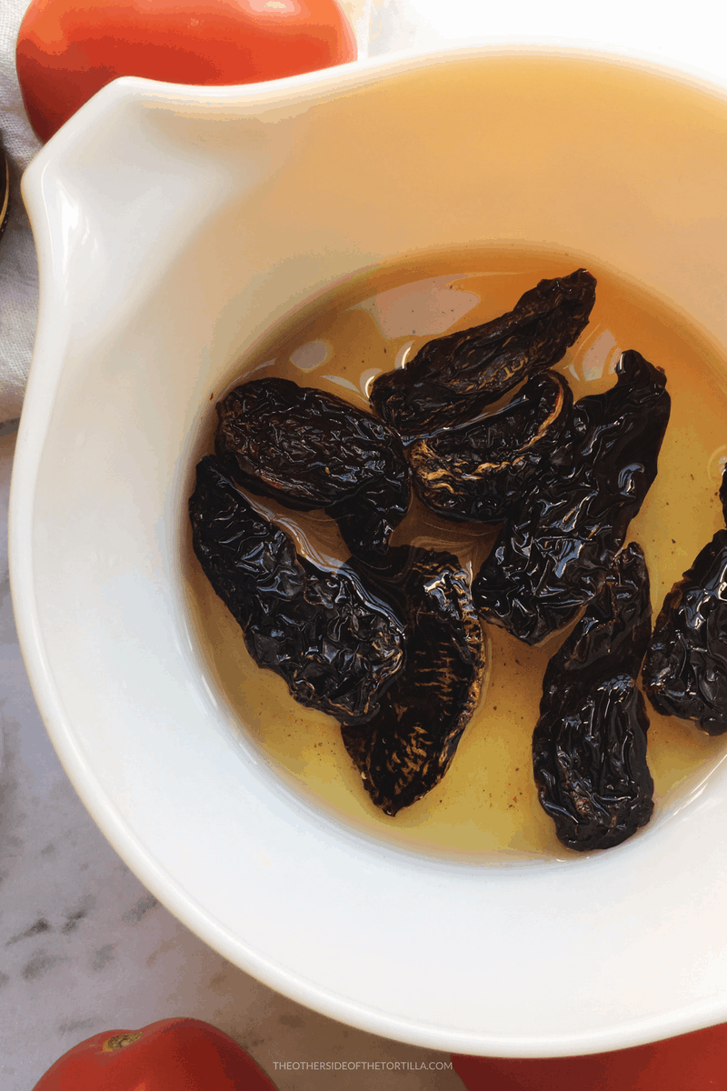 Rehydrating dried chile morita for chicharrón guisado via theothersideofthetortilla.com