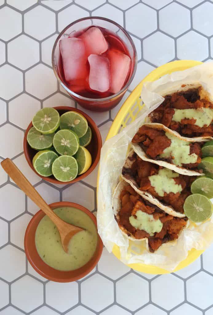 chicharrón guisado tacos with jamaica to drink, limes and salsa
