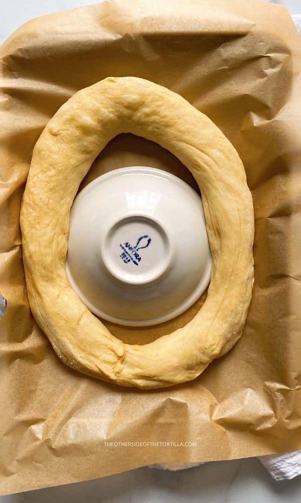 dough shaped in an oval ring around a ceramic dish on top of parchment paper