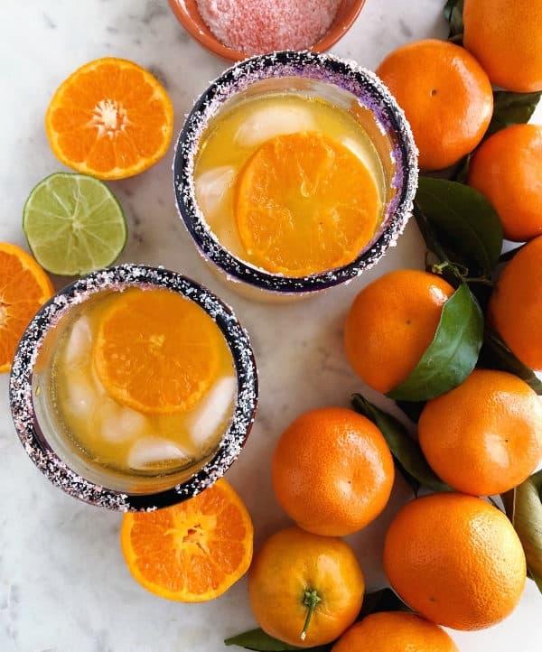 Mandarin orange margarita in a glass rimmed with chamoy salt