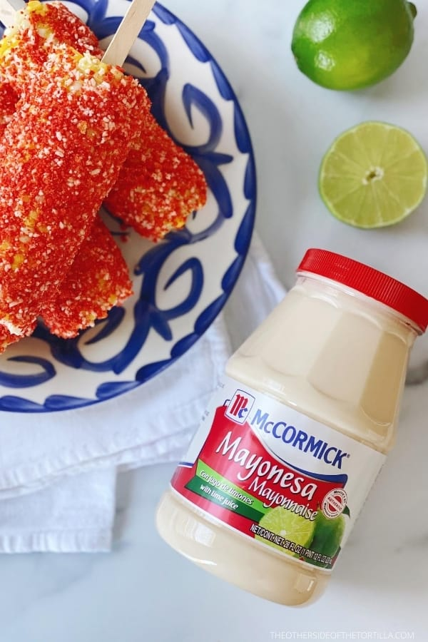 Mexican elotes locos on a blue and white talavera plate on top of a white kitchen towel surrounded by a mayonnaise jar and limes