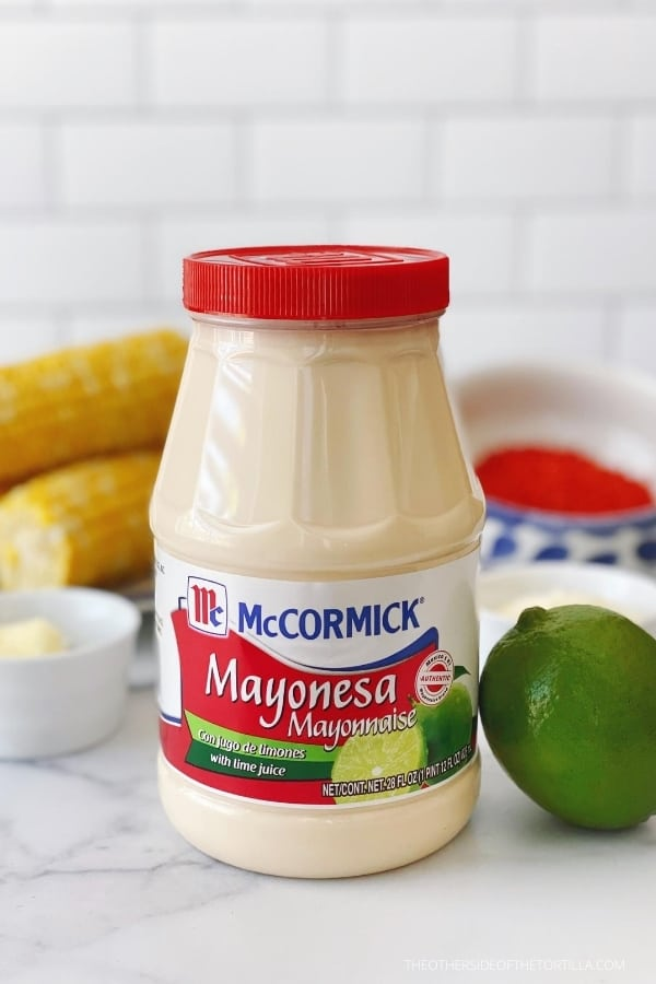 McCormick Mayonesa with lime juice on a marble countertop with a lime leaning against the jar and corn cobs in the background