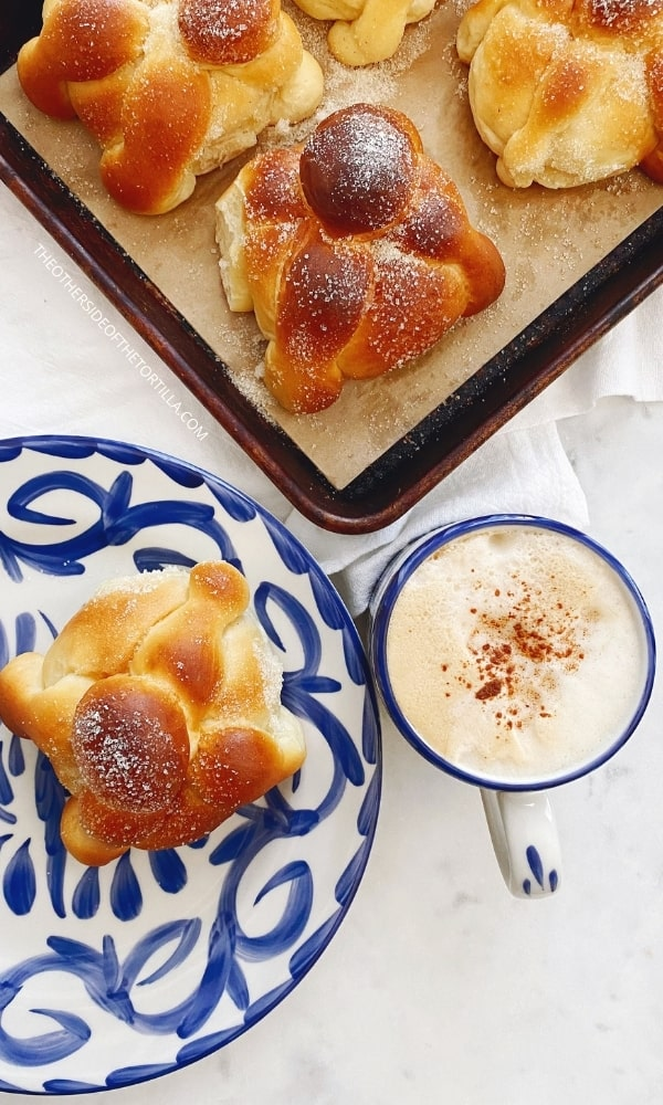 Mexican pan de muerto on a baking sheet and on a talavera ceramic plate with a cup of coffee