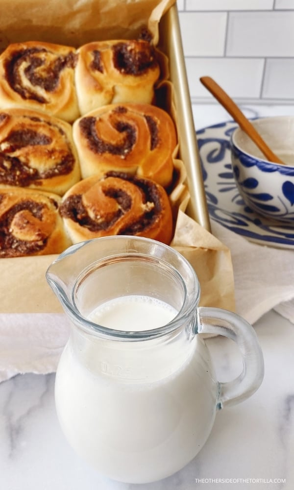 milk in a pitcher in the foreground in front of a pan of mexican cinnamon rolls fresh from the oven