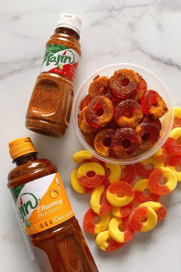 Clockwise from top left: bottle of Tajín; chamoy peach rings, plain peach ring gummies, Tajín brand chamoy sauce