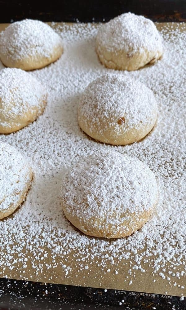 Mexican wedding cookies sprinkled with powdered sugar on a baking tray